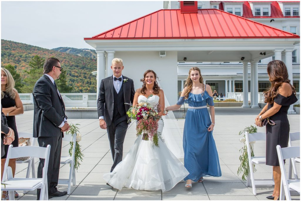 Bride being escorted down the aisle - An Omni Mount Washington Resort Wedding for a Blended Family