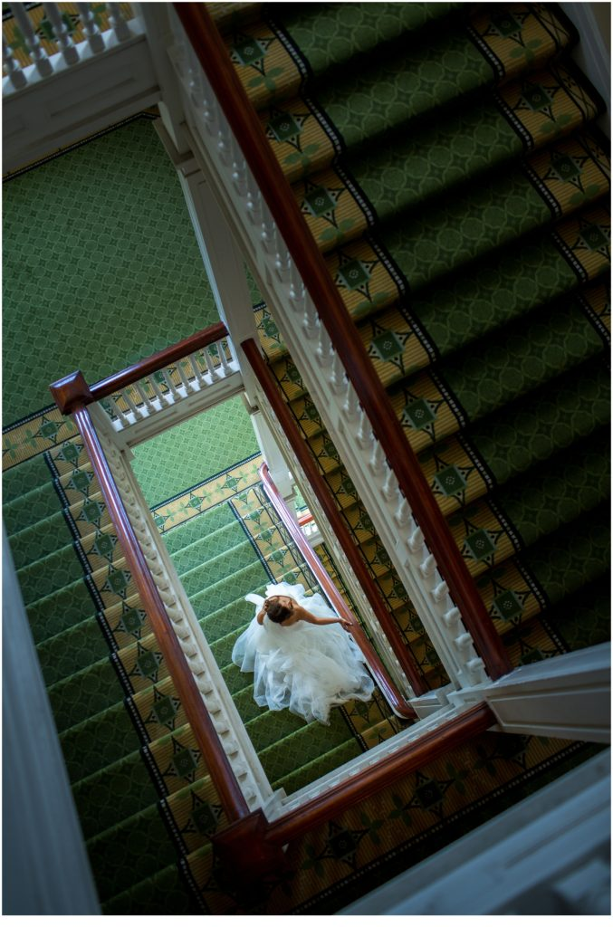 Bride walking down the stairs from above - An Omni Mount Washington Resort Wedding for a Blended Family