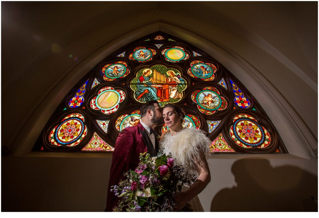 Bride and groom in front of stained glass windows - A Vintage-Inspired Winter Wedding at Agora Grand