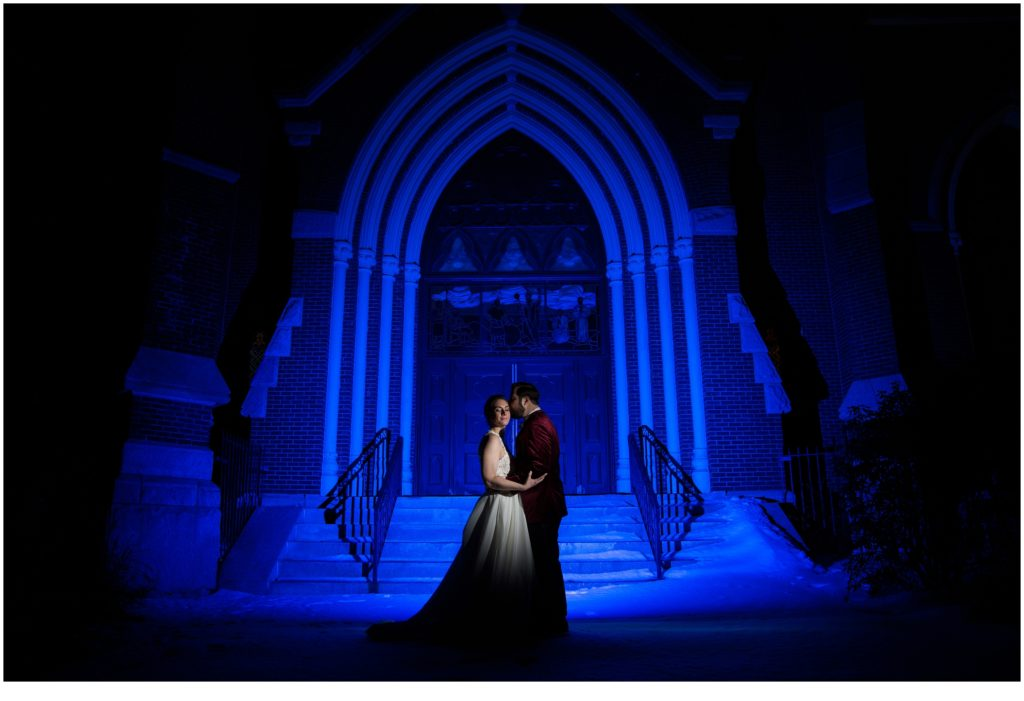 epic shot of bride and groom in front of arched door lit by blue light  - A Vintage-Inspired Winter Wedding at Agora Grand
