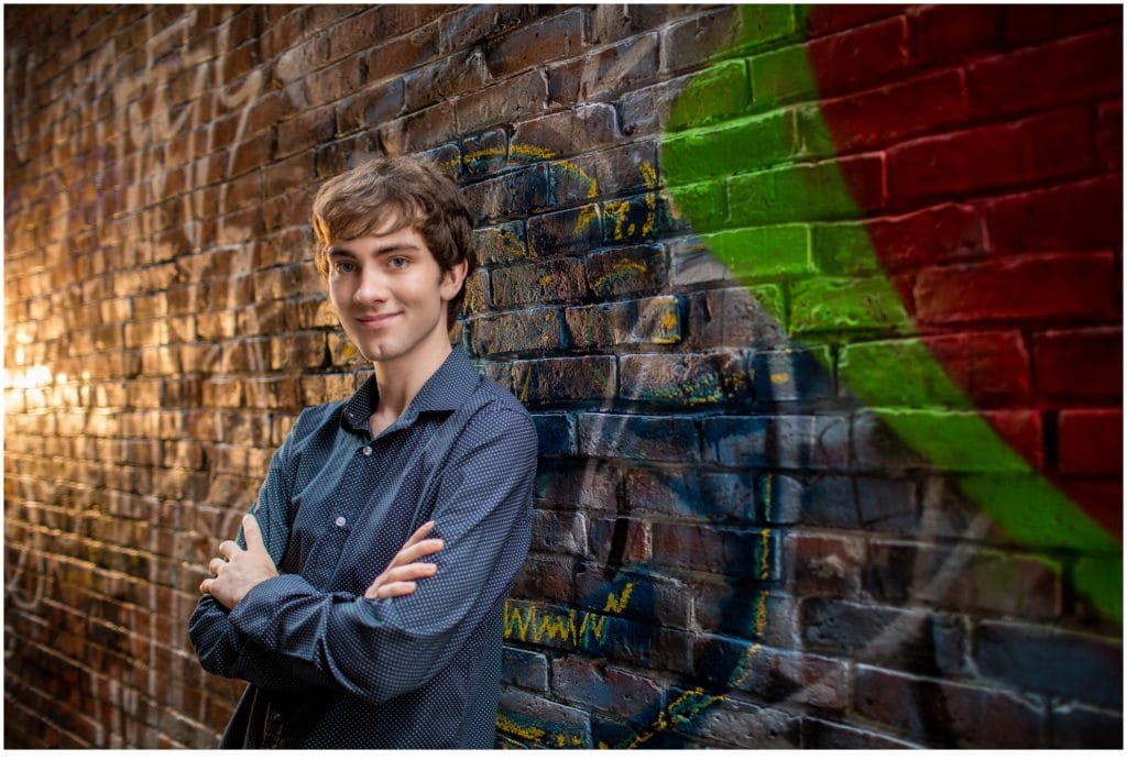 2021 Hall-Dale Senior, Nick, Leaning against brick wall with Graffiti on it